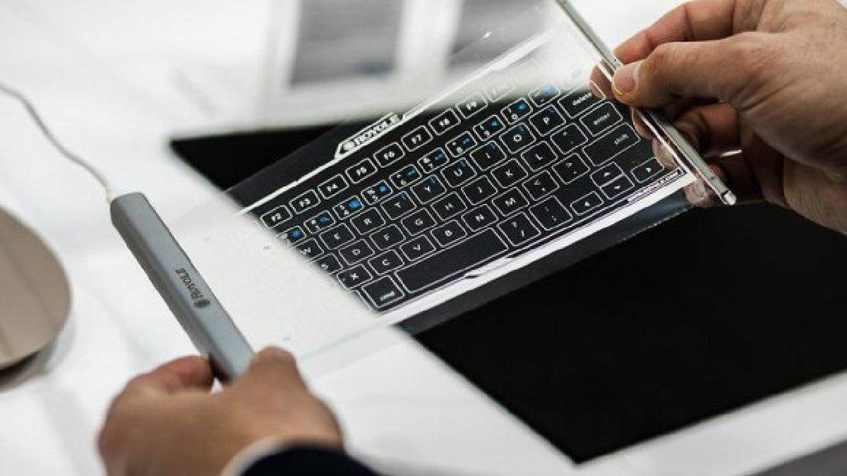 Клавиатура выглядит как металлический тубус, из которого вытягивается прозрачная плёнка с нарисованными клавишами с буквами
